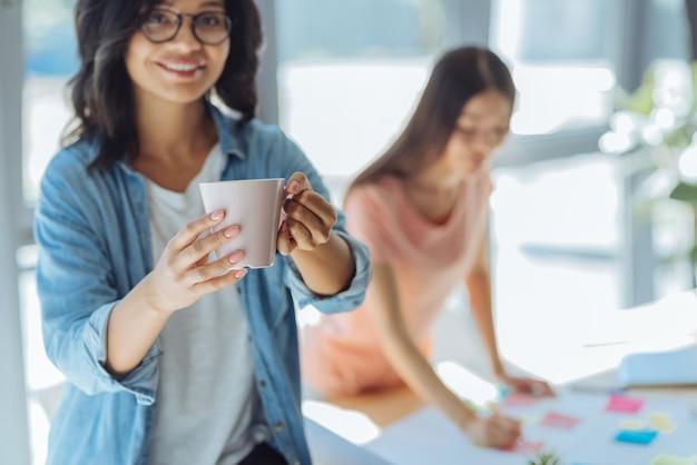 心地よい飲み物。仕事を休んでいる間、素敵な陽気な賢い女性によって保持されているお茶とカップの選択的な焦点