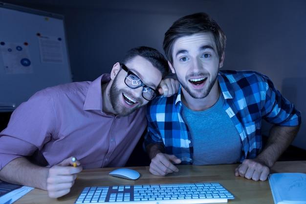 楽しい感情。ノートパソコンの画面を見て、面白いものを見ながら笑っている幸せなポジティブハンサムな男