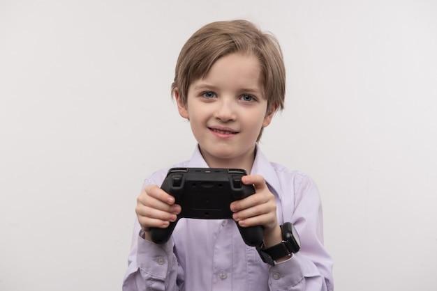 Приятное развлечение. счастливый довольный мальчик держит игровую консоль во время видеоигр