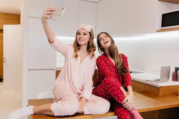 Приятные европейские девушки делают селфи перед завтраком. крытый выстрел довольно белокурой молодой женщины фотографируя с телефоном на кухне.