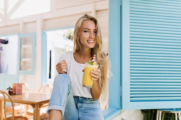 ジュースのガラスとカフェに座っている楽しい金髪の女性。カクテルでポーズをとっている間笑っている白いtシャツの驚くべき日焼けした女性。