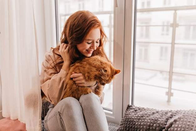 Pleasant female model holding red cat on her knees. indoor portrait of charming ginger woman posing with pet.