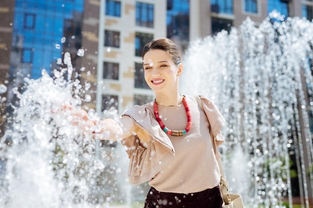 Приятная свежесть. позитивная довольная женщина, чувствуя брызги воды, стоя возле фонтана