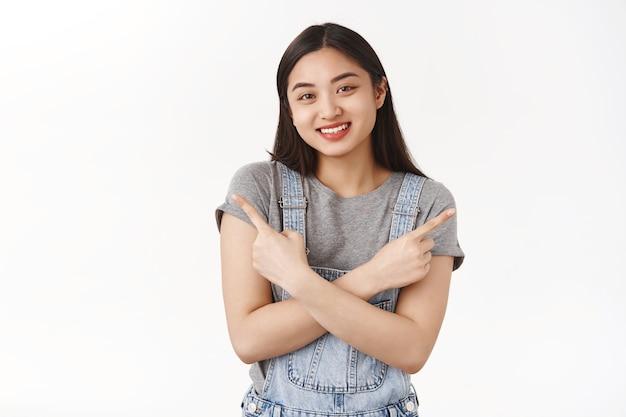 Приятная дружелюбная жизнерадостная улыбающаяся азиатская брюнетка женщина скрестив руки на груди, указывающая боком влево и вправо, прося помочь сделать выбор, улыбается счастливо, радостно, делая покупки, есть несколько вариантов белая стена