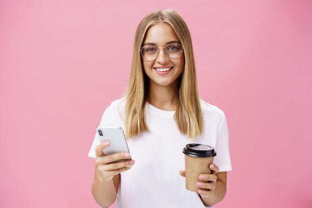 Приятная дружелюбная девушка улыбается на камеру, держа бумажный стаканчик с кофе и смартфон. портрет радостной красивой женщины, пьющей утренний напиток, излагает мнение о кафе в интернете над розовой стеной