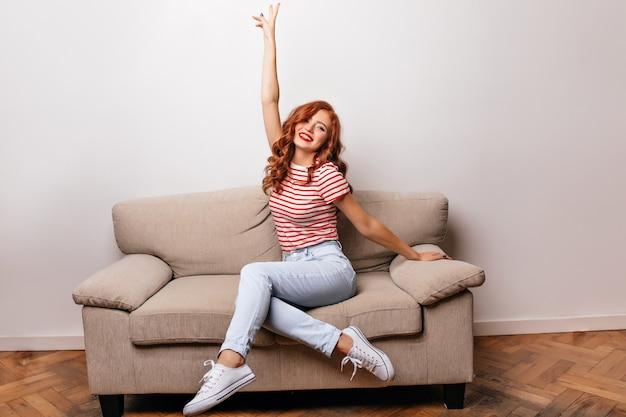 Приятная девушка в белых туфлях сидит на диване и смеется. красивая рыжая женская модель с вьющейся прической охлаждает в ее квартире.