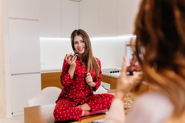 Piacevole ragazza in pigiama rosso seduto con le gambe piegate mentre la sua amica scatta foto. ritratto dell'interno della signora sorridente che posa sul tavolo davanti alla sorella che utilizza il telefono per il servizio fotografico.
