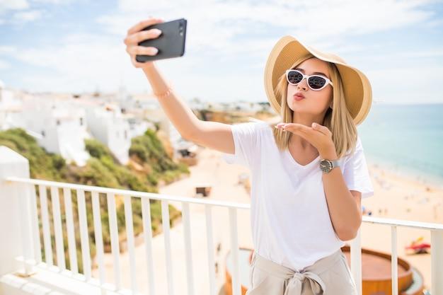 Piacevole ragazza in occhiali da sole e cappello manda baci mentre fa selfie sul mare