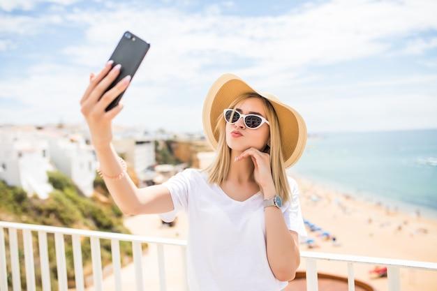 Piacevole ragazza in occhiali da sole e cappello che tocca la sua guancia mentre fa selfie sul mare