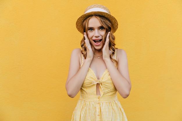 즐거운 소녀는 흰색 리본으로 장식 된 밀짚 모자를 착용합니다. 여름 옷 서에서 화려한 젊은 여자.