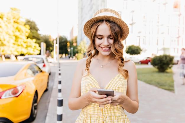 Приятная гламурная девушка стоит на улице и пишет текстовое сообщение. открытый портрет очаровательной женщины в ретро шляпе, позирующей со смартфоном.