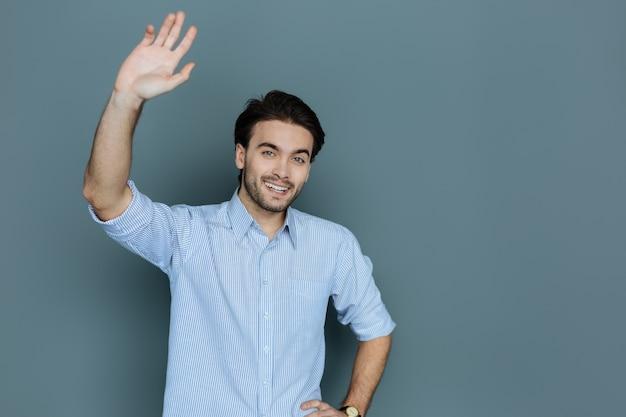 즐거운 인사. 웃고 당신을 인사하는 동안 그의 손을 잡고 긍정적 인 즐거운 친절한 남자