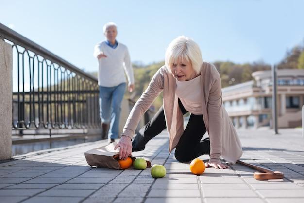 Приятная седовласая грустная дама, стоящая на коленях на земле с овощами, в то время как мужчина средних лет идет к ней