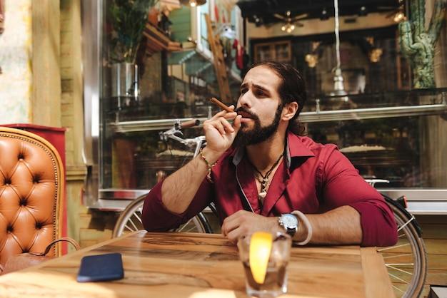 Приятный красавец держит сигару во время курения