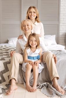유쾌한 행복한 대가족이 줄을 서서 키가 작은 것부터 가장 큰 것까지, 사진을 위해 포즈를 취하고 정면에서 넓게 웃고 있습니다.