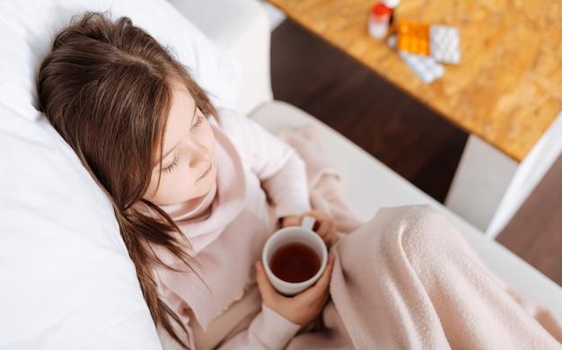 Приятная больная девушка пьет чай и чувствует себя больным во время отдыха дома