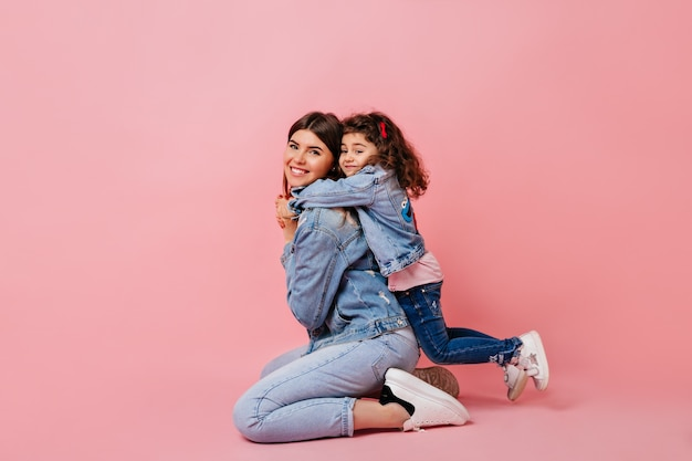 Pleasant kid embracing mother on pink background. studio shot of blissful mom and little daughter in jeans.
