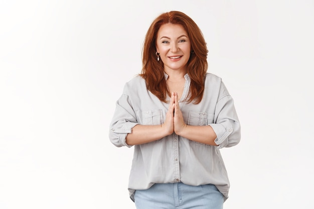 Pleasant kind tender middle-aged redhead 50s woman hold hands pray palms together chest thankful supplicating smiling toothy glad appreciate sincere help, standing white wall