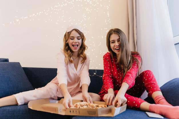 Приятные дамы в пижамах веселятся вместе. улыбающиеся сестры едят пиццу рано утром.