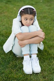 Приятного досуга. детские наушники слушают музыку. мода довольно крутая девушка в наушниках, слушая музыку. слушайте музыку, отдыхая на открытом воздухе. малыш девочка наслаждается музыкой, сидя на лугу с зеленой травой.
