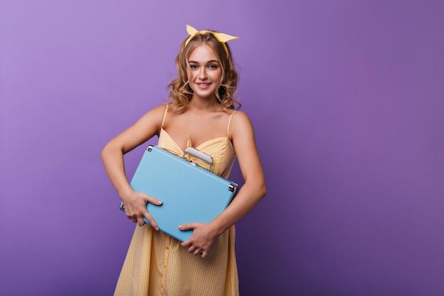 Piacevole donna leggermente abbronzata che tiene la sua valigia blu. modello femminile ottimista con nastro giallo in posa con bagagli sulla viola.