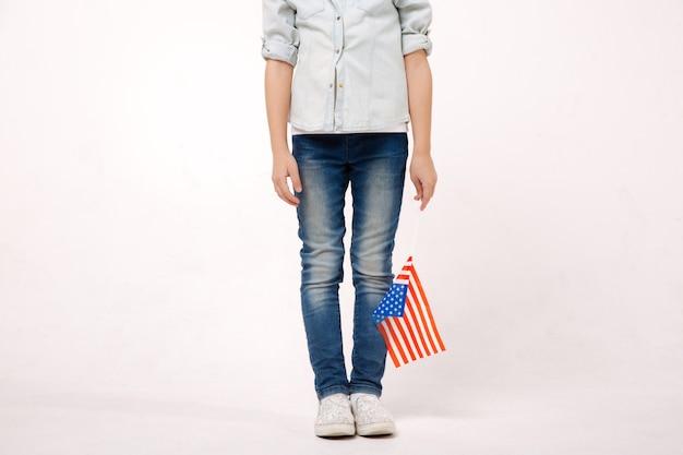 Приятный маленький застенчивый ребенок держит американский флаг, выражая положительные эмоции и стоя у белой стены