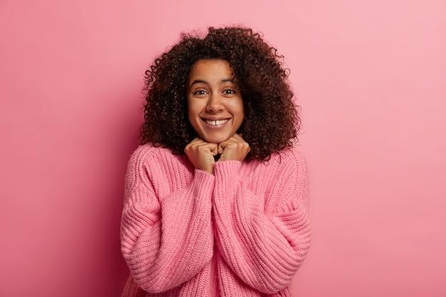 見栄えの良いアフロの女性は優しく微笑んで、両手をあごの下に置き、健康な肌を持ち、冬のセーターを着て、前向きなニュースを受け取り、ピンクの壁に隔離されています。