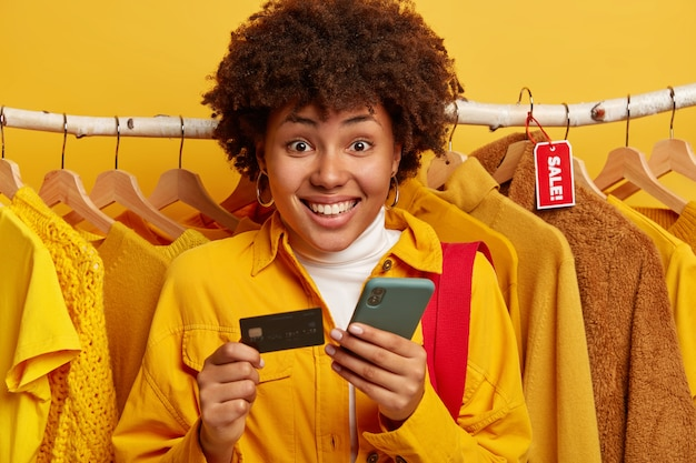 Pleasant looking afro woman verifies bank account, pays online via smartphone, holds credit card