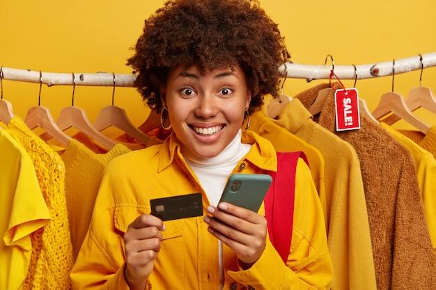 見栄えの良いアフロの女性が銀行口座を確認し、スマートフォンを介してオンラインで支払い、クレジットカードを保持します