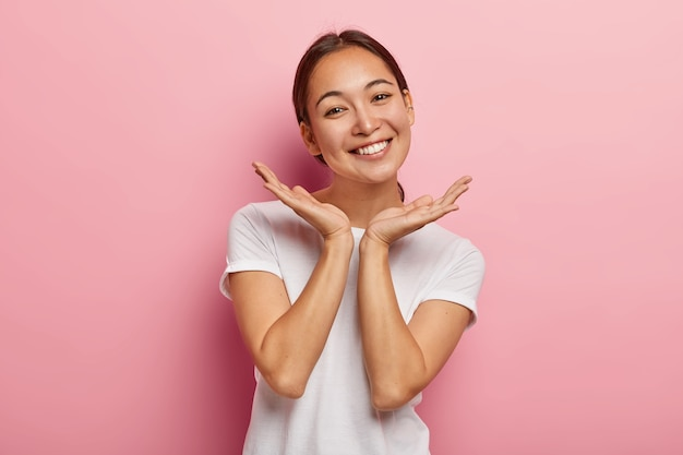 Pleasant looking asian female model smiles gladfully, spreads palms near face, expresses positive emotions, wears white t shirt, has appealing appearance, healthy skin, isolated on pink  wall