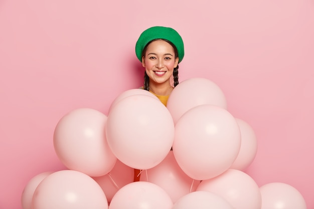 Pleasant looking asian female model wears green beret, stands near many balloons, poses over pink background, celebrates birthday