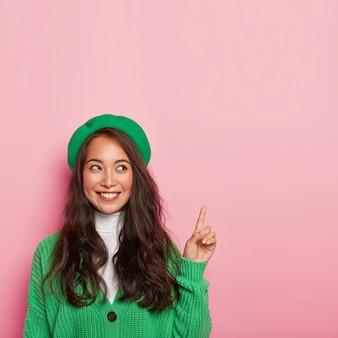 유쾌한 아시아 여성은 녹색 베레모와 니트 점퍼를 입고 앞쪽 손가락을 가리키며 쾌활한 표정을 지닙니다.