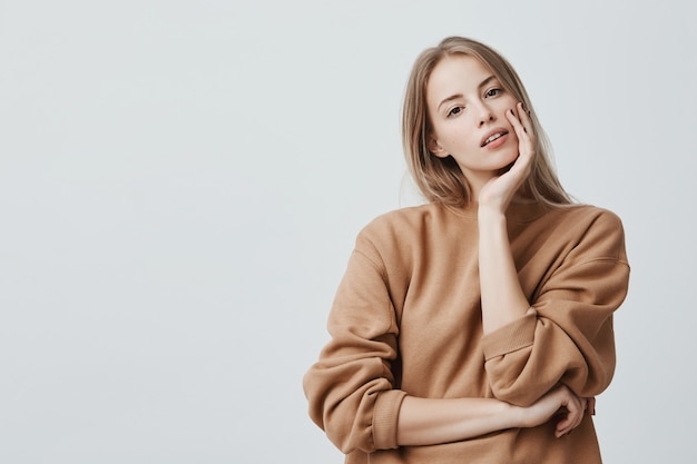 Pleasant looking attractive blonde woman dressed in beige loose sweater with appealing dark eyes and parted lips