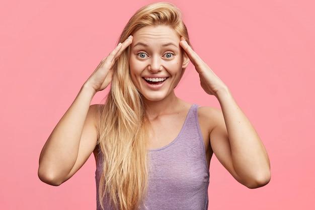 Приятно выглядящая блондинка голубоглазая молодая модель со счастливым выражением лица держит руки на голове, вспоминает некоторые положительные моменты жизни, одетая в повседневную футболку.