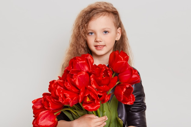 Pleasant looking blonde wavy haired child in black leather jacket, looking at front with smile, embracing red tulips in hands