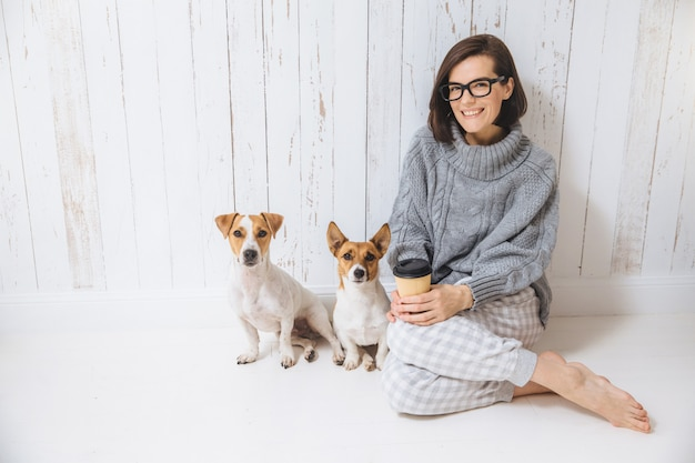 Pleasant looking brunette female dressed casually, drinks hot beverage from paper cup, sits near two dogs