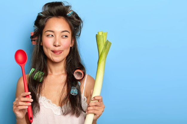 Pleasant looking brunette housewife with asian appearance, holds spoon and green leek, prepares vegetarian breakfast