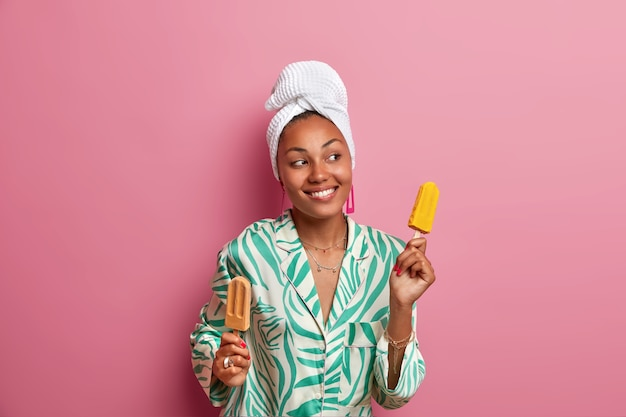 Pleasant looking carefree dark skinned woman dances with ice cream in hands, has good mood, looks aside and smiles broadly, wears towel and dressing gown, eats cold frozen dessert during summer