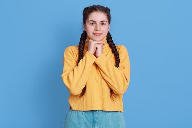 心地よい表情の白人女性は、魅力的な笑顔と魅力的な表情を持ち、あごの下で拳を握りしめ、青い壁に立ち向かいます