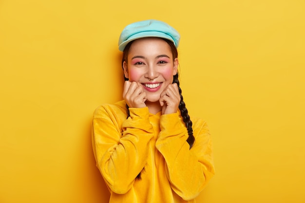 Pleasant looking cheerful asian girl keeps both hands under chin, has pinup makeup, wears blue stylish cap, velvet yellow hoodie