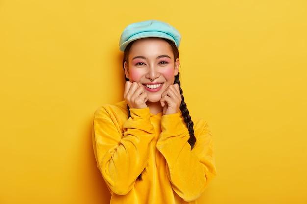 Una ragazza asiatica allegra e dall'aspetto piacevole tiene entrambe le mani sotto il mento, ha il trucco pinup, indossa un berretto blu elegante, felpa con cappuccio giallo velluto