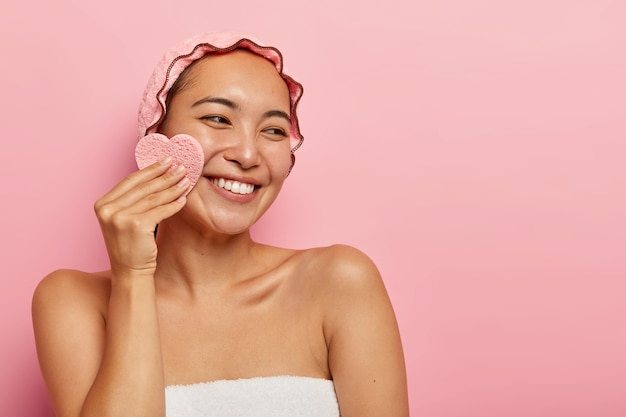 Pleasant looking cheerful asian woman wipes face with cosmetic sponge, removes makeup, looks on right side, wears waterproof protective headgear, has tender smile, white teeth