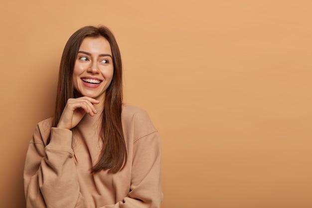 유쾌하고 쾌활한 갈색 머리 여자가 매력적인 미소로 옆으로 보이고, 턱 아래에 손을 유지하고, 캐주얼 스웨트 셔츠를 입고, 베이지 색 벽에 포즈를 취하고, 재미있는 이벤트를 기억하고, 즐거운 표정을 가지고 있습니다.