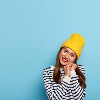 유쾌하고 쾌활한 여자는 머리를 기울이고 부드러운 미소를 지으며 턱 근처에 손을 모으고 노란색 모자와 줄무늬 선원 점퍼를 착용합니다.