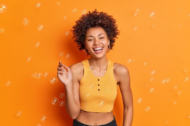 Приятно выглядящая жизнерадостная молодая афроамериканская девочка-подросток держит широко поднятую руку, широко улыбается, имеет беззаботное выражение, носит повседневную одежду, позирует у оранжевой стены с летающими мыльными пузырями
