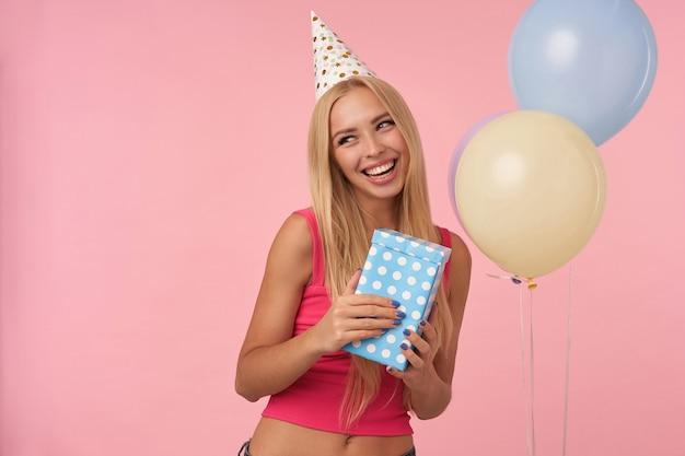 Piacevole cerca allegro giovane femmina bionda che indossa top rosa e cappello a cono di vacanza mentre si trova su sfondo rosa, rallegrandosi mentre posa in mongolfiere multicolori