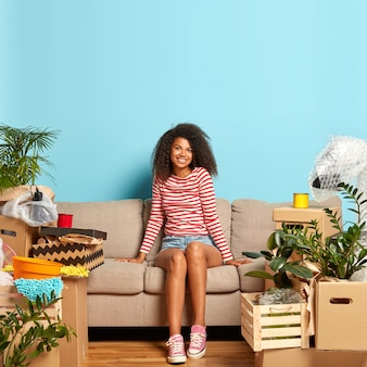 La donna afro riccia dall'aspetto piacevole indossa pantaloncini di jeans e maglione a righe, si siede sul divano, circondata da molte scatole