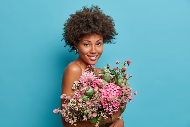 Pleasant looking curly woman gets natural gift, carries beautiful bouquet of flowers