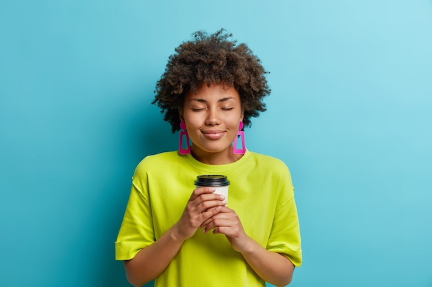 즐거운 찾고 곱슬 젊은 여자가 눈을 감고 테이크 아웃 커피를 즐긴다. 쾌락은 여가 시간이 파란색 벽 위에 고립 된 캐주얼 티셔츠와 핑크색 귀걸이를 착용하고있다.