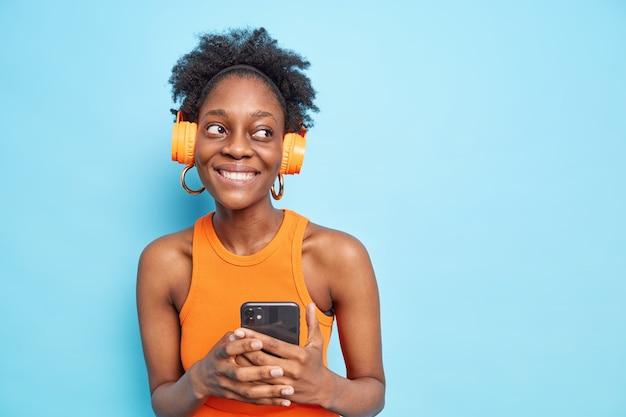 Pleasant looking dark skinned teenage girl with natural curly hair looks away smiles toothily holds modern smartphone listens to  favorite music via wireless headphones